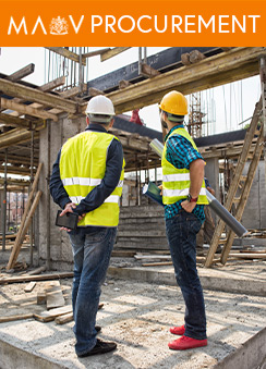 A photograph of two workmen looking at a building under construction