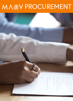 A close-up photo of a person's hand writing on paper