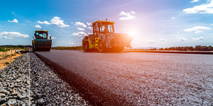 Photo of two tractors laying a road