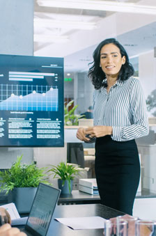 A woman standing in front of a TV monitor making a presentation