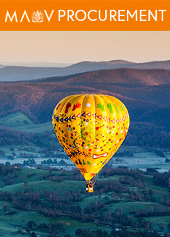 A hot air balloon floating over a lush green mountainous landscape