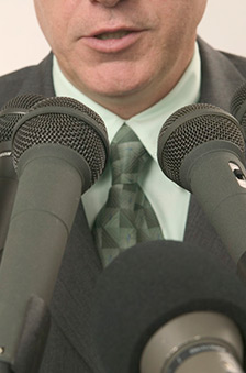 A photograph of a person speaking to three different microphones
