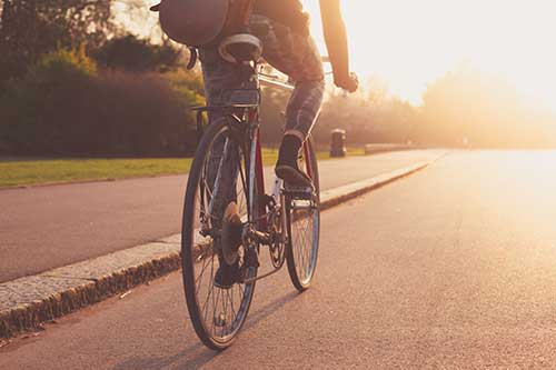 Rear-view of person riding a bicycle into the sunset