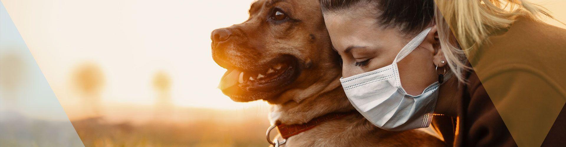 Picture of a woman wearing a face mask with her dog.