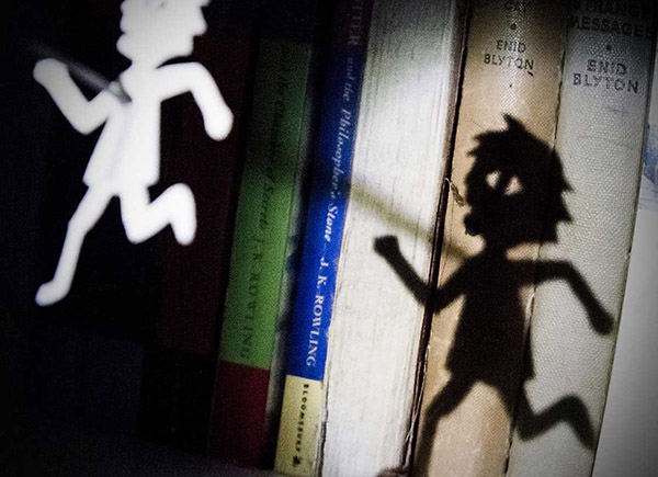 Image of a cut-out doll reflected on children's books