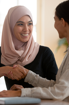 Happy asian muslim businesswoman sales manager shake hand of caucasian lady client make deal with female customer at meeting with laptop, diverse women partnership, respect and collaboration concept